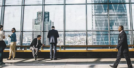 People in front of a large window of a city skyline